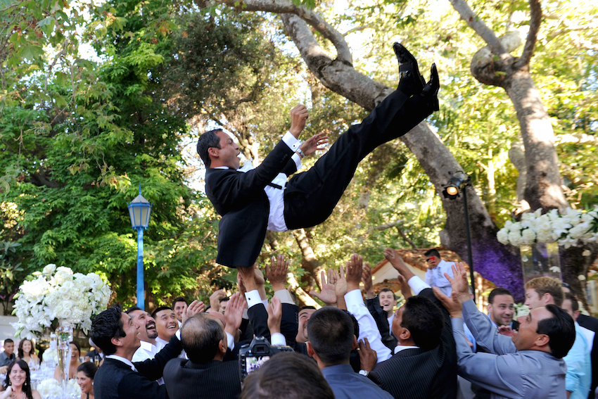 Groom being tossed by wedding guests