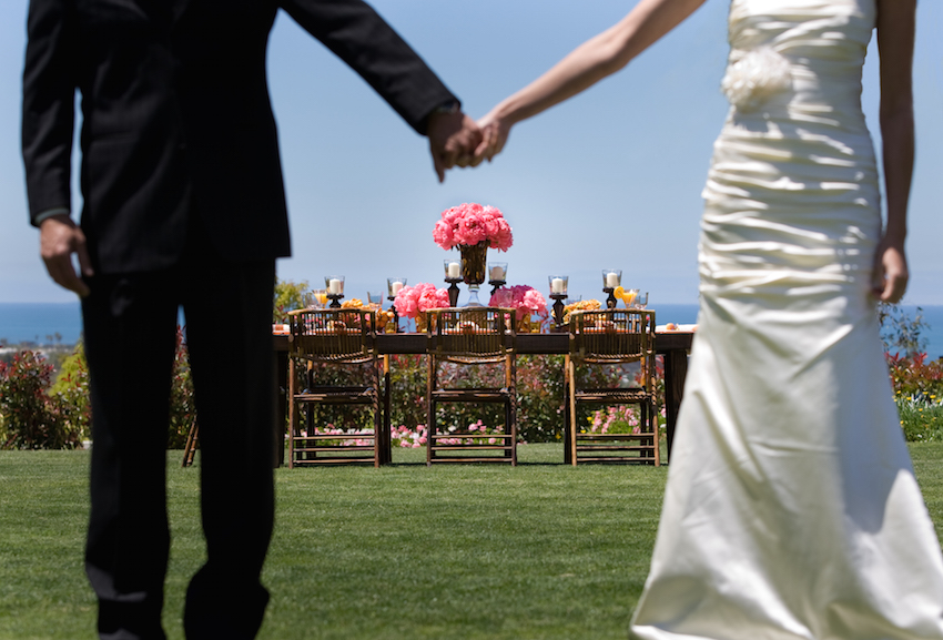 Bride and groom hold hands at outdoor reception