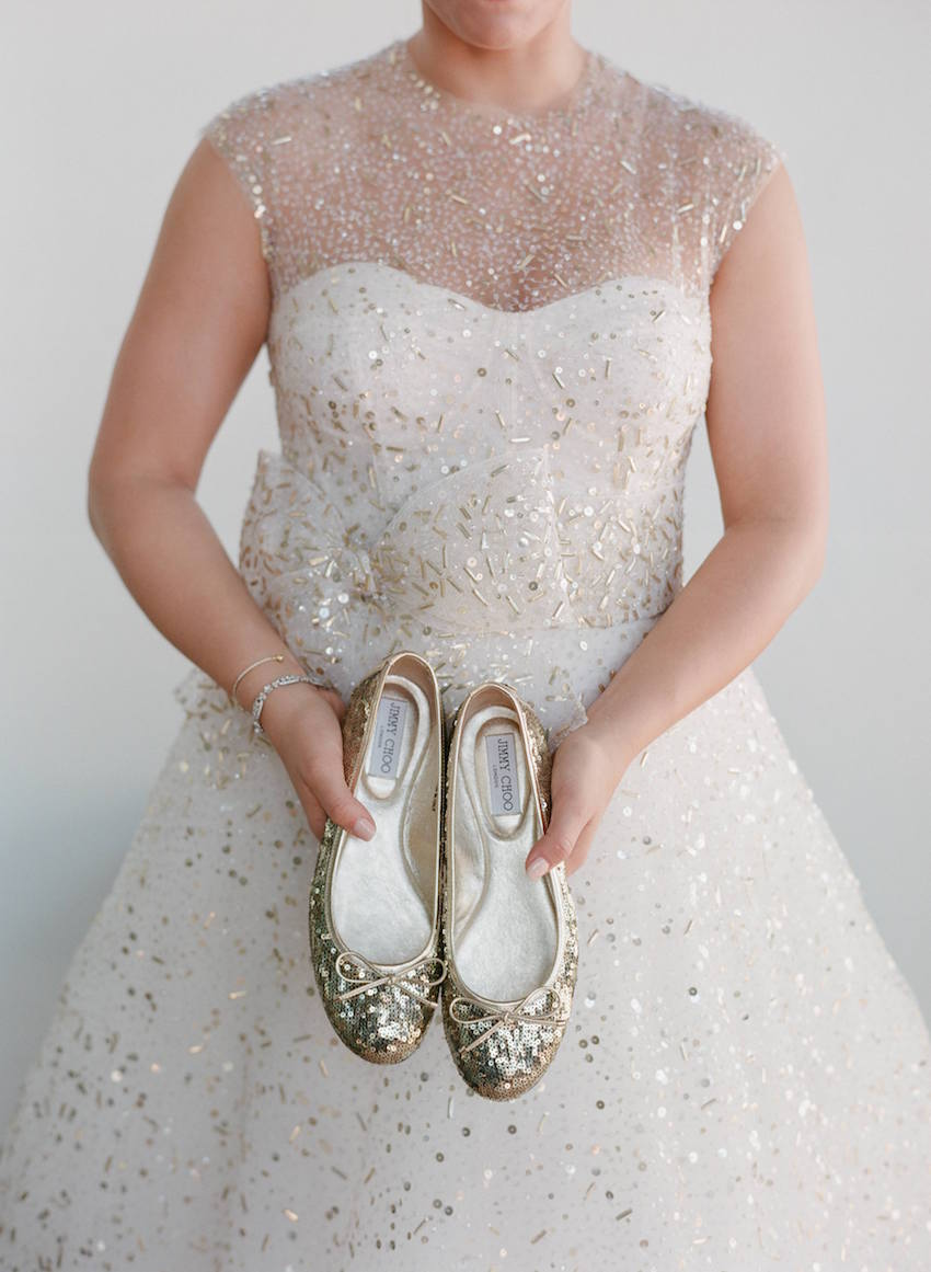Bride holding gold sequin flats in gold dress