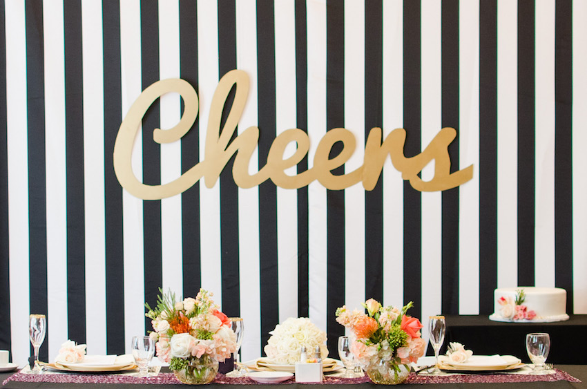 Gold Cheers sign on black and white stripes