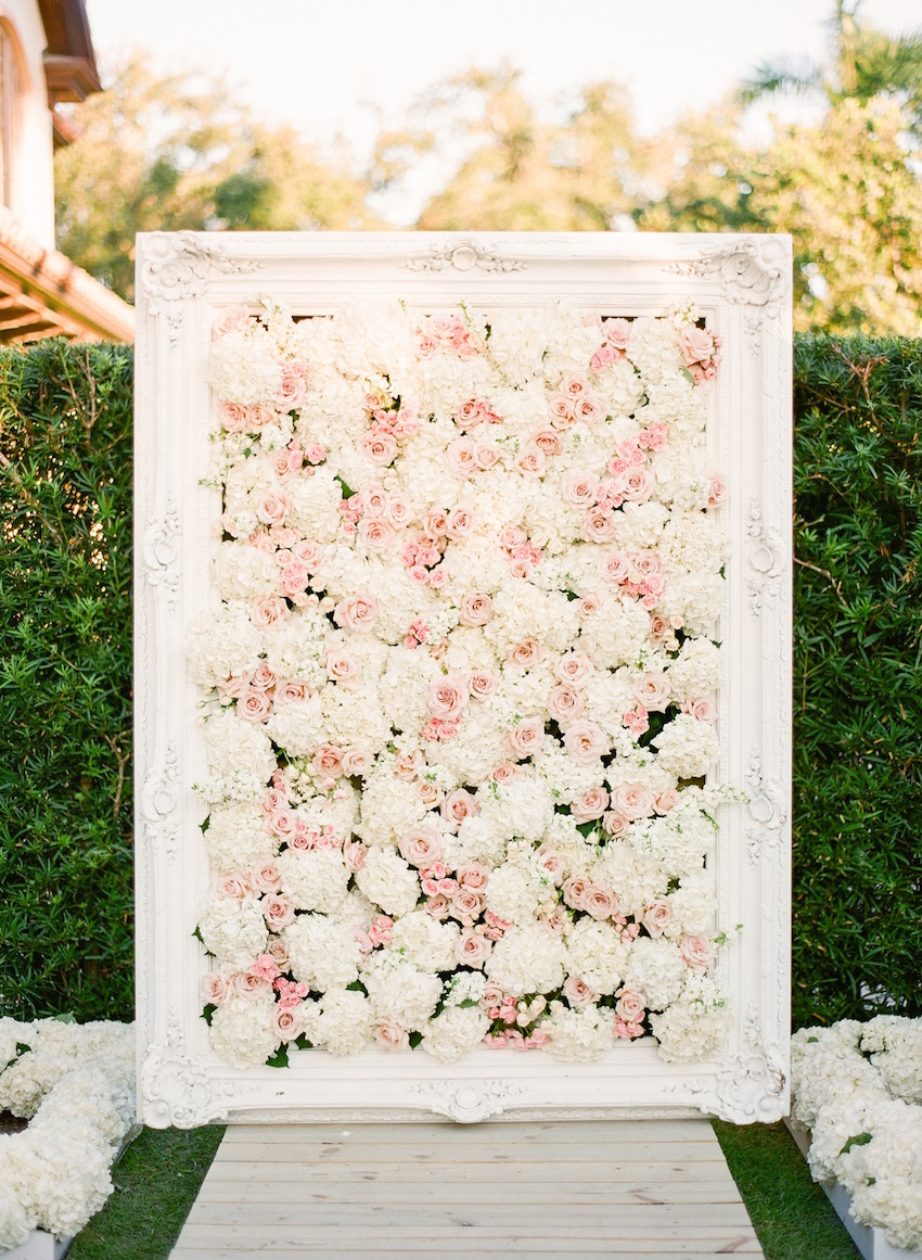 Pink and white flower wall at wedding ceremony