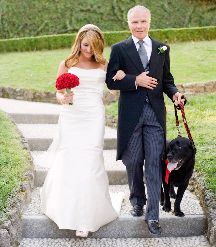 Bride and father of bride walking dog at wedding