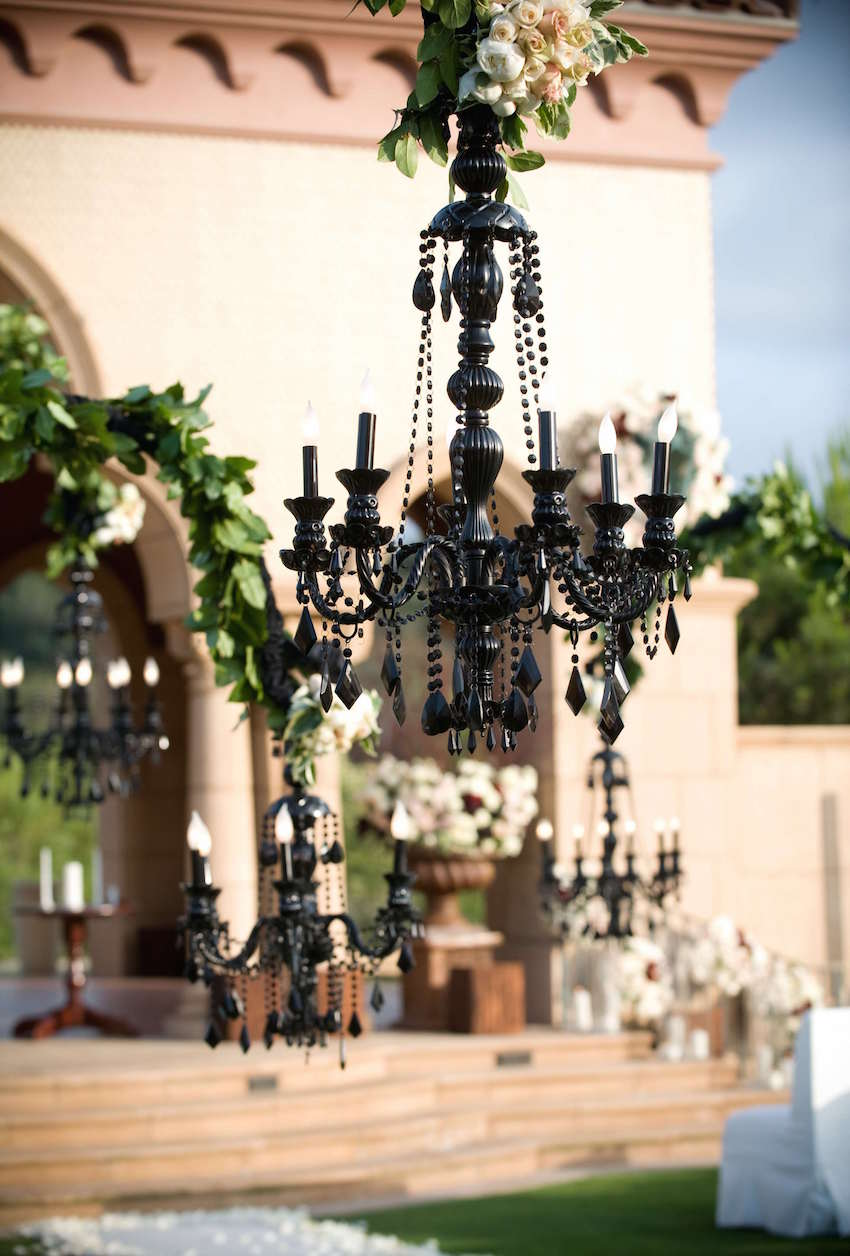 Black chandelier with flowers on top at wedding ceremony