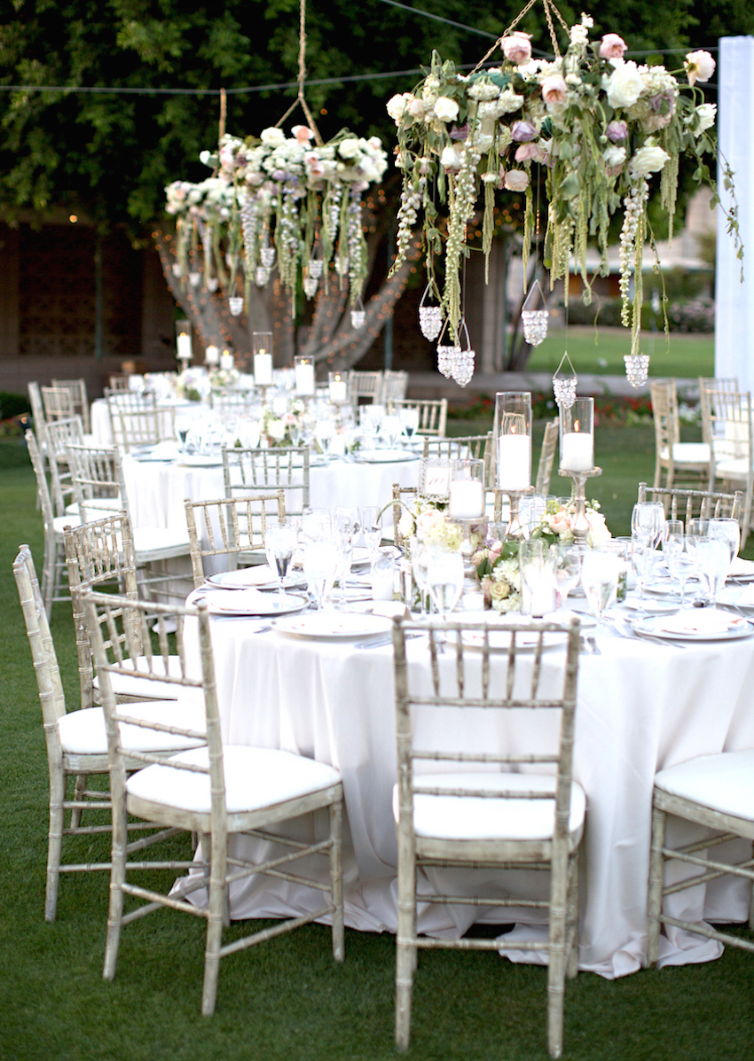 Floral chandelier above table at outdoor wedding