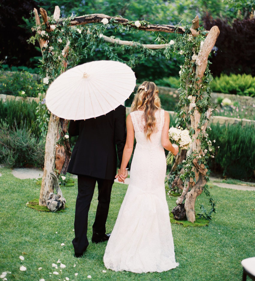 Bride and groom with parasol at outdoor rustic wedding