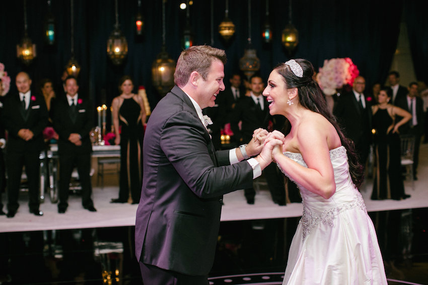 Bride and groom grab each other's hands on dance floor