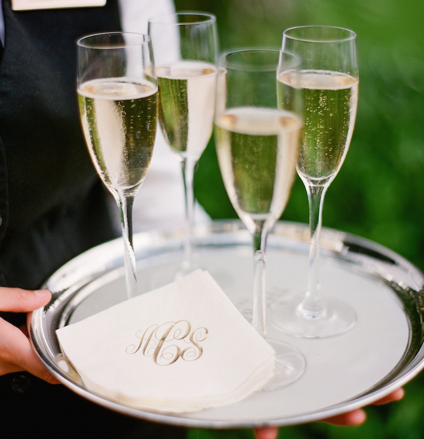 Gold monogram on cocktail napkin with champagne