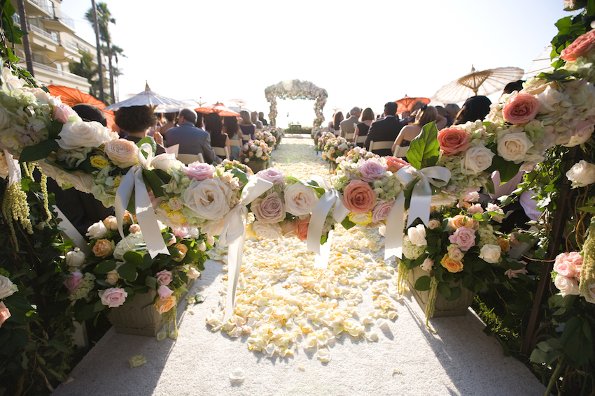 Parasols at outdoor peach and white ceremony