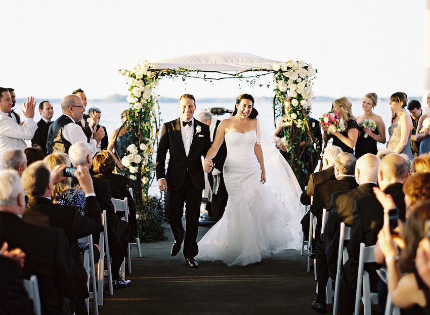 Bride and groom walking down pier aisle
