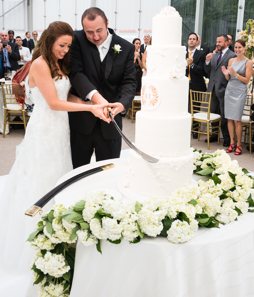Bride and groom cutting cake with saber