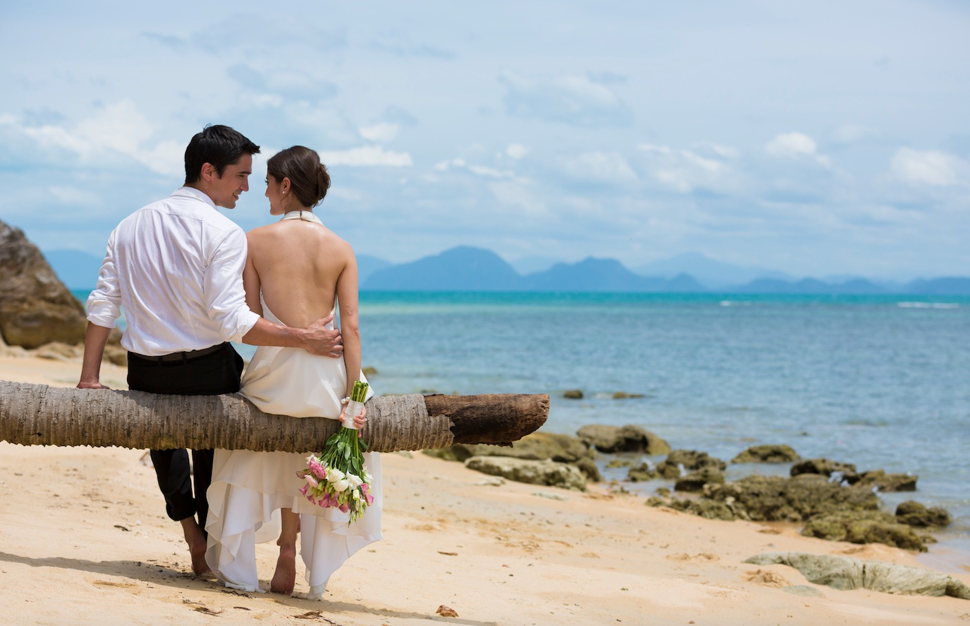 Bride and groom on palm tree in Thailand