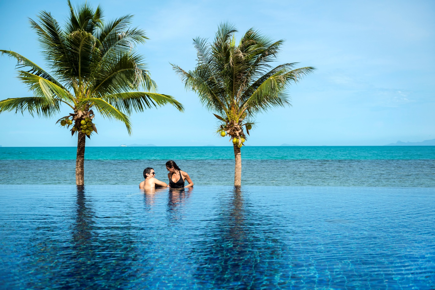 Bride and groom in infinity swimming pool