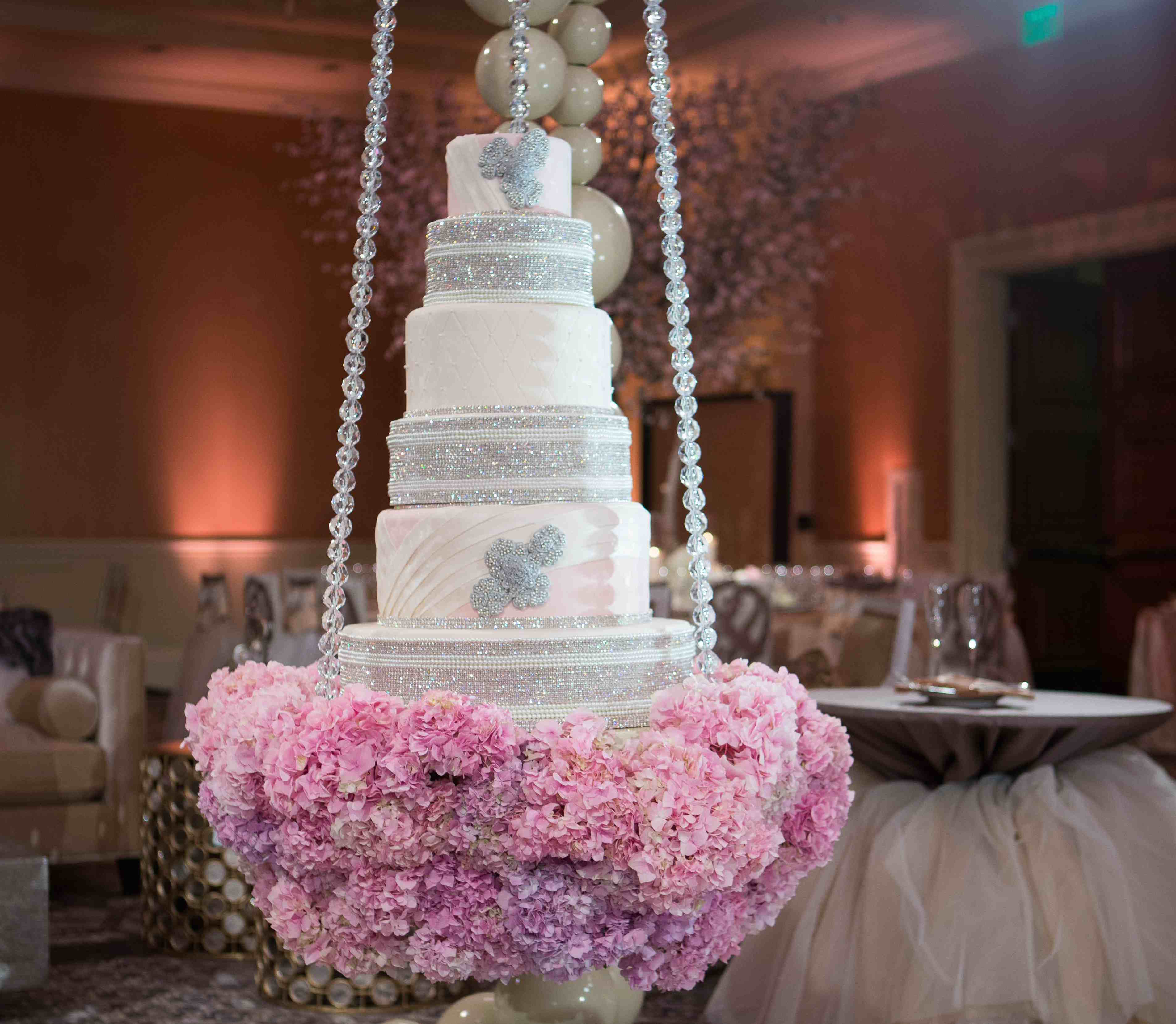 Pink hydrangeas at bottom of Tamra Barney wedding cake swing