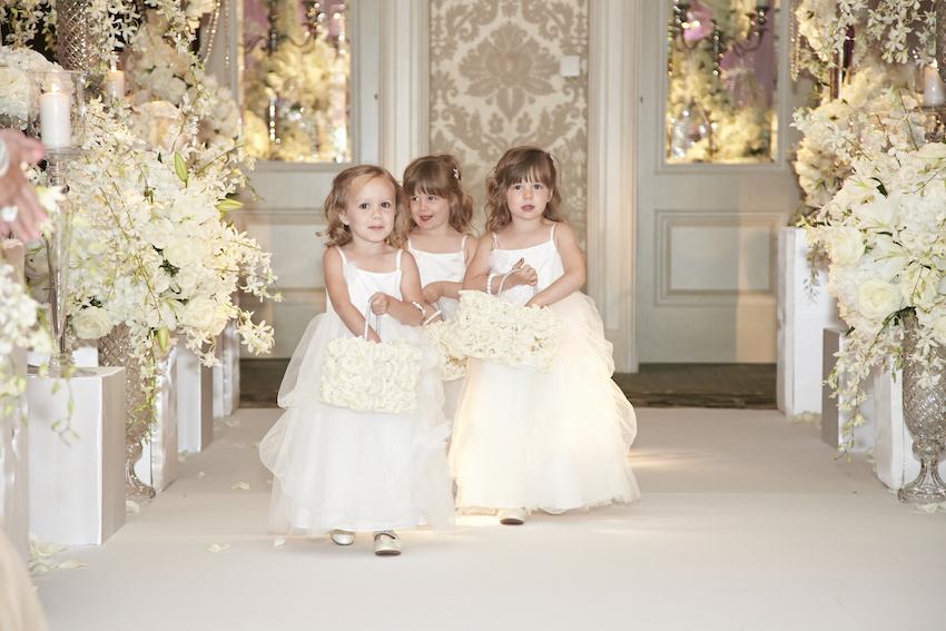 Flower girls walking down aisle at wedding
