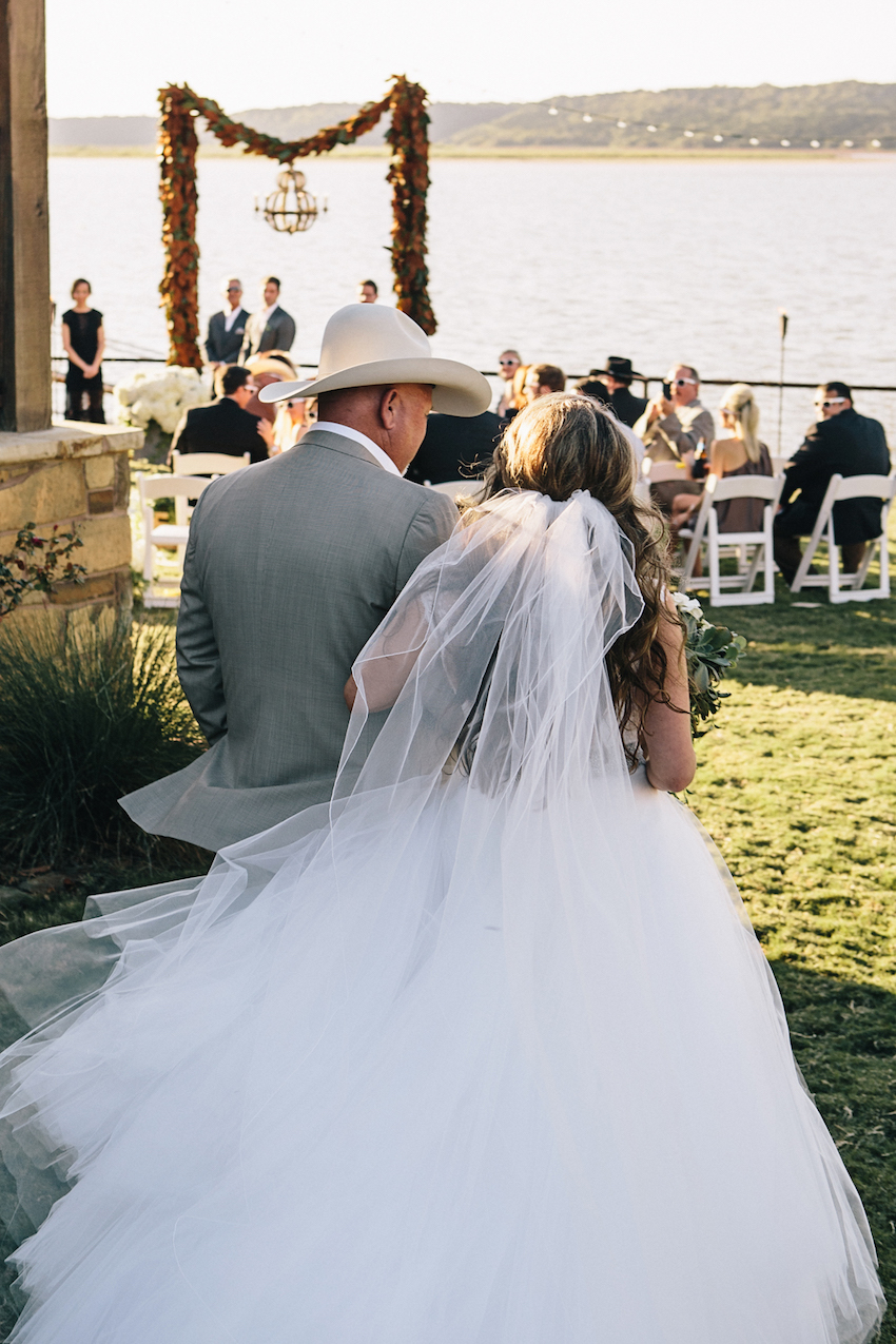 Bride with cowboy father of bride walking down aisle