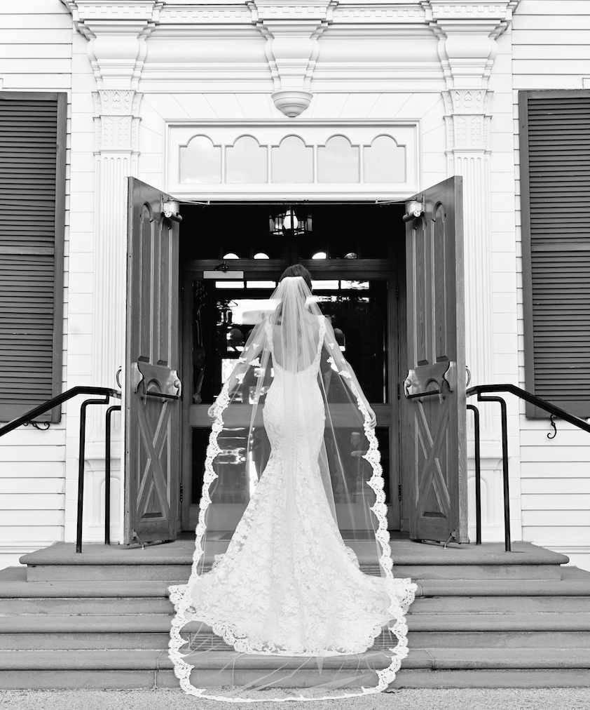 Black and white photo of bride in front of church