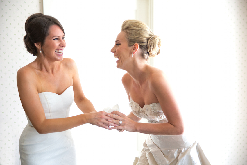 Bride laughing with bridesmaid in white dress