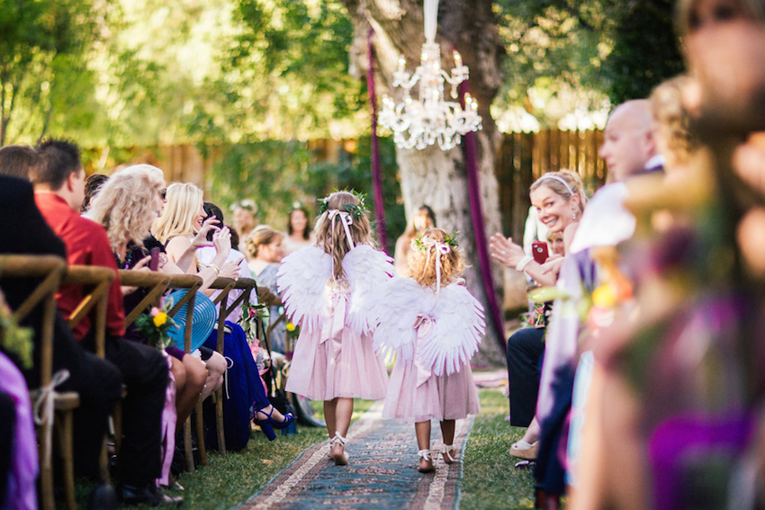 Flower girls with fairy wings at bohemian wedding