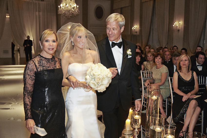 Bride walks down aisle with parents at wedding