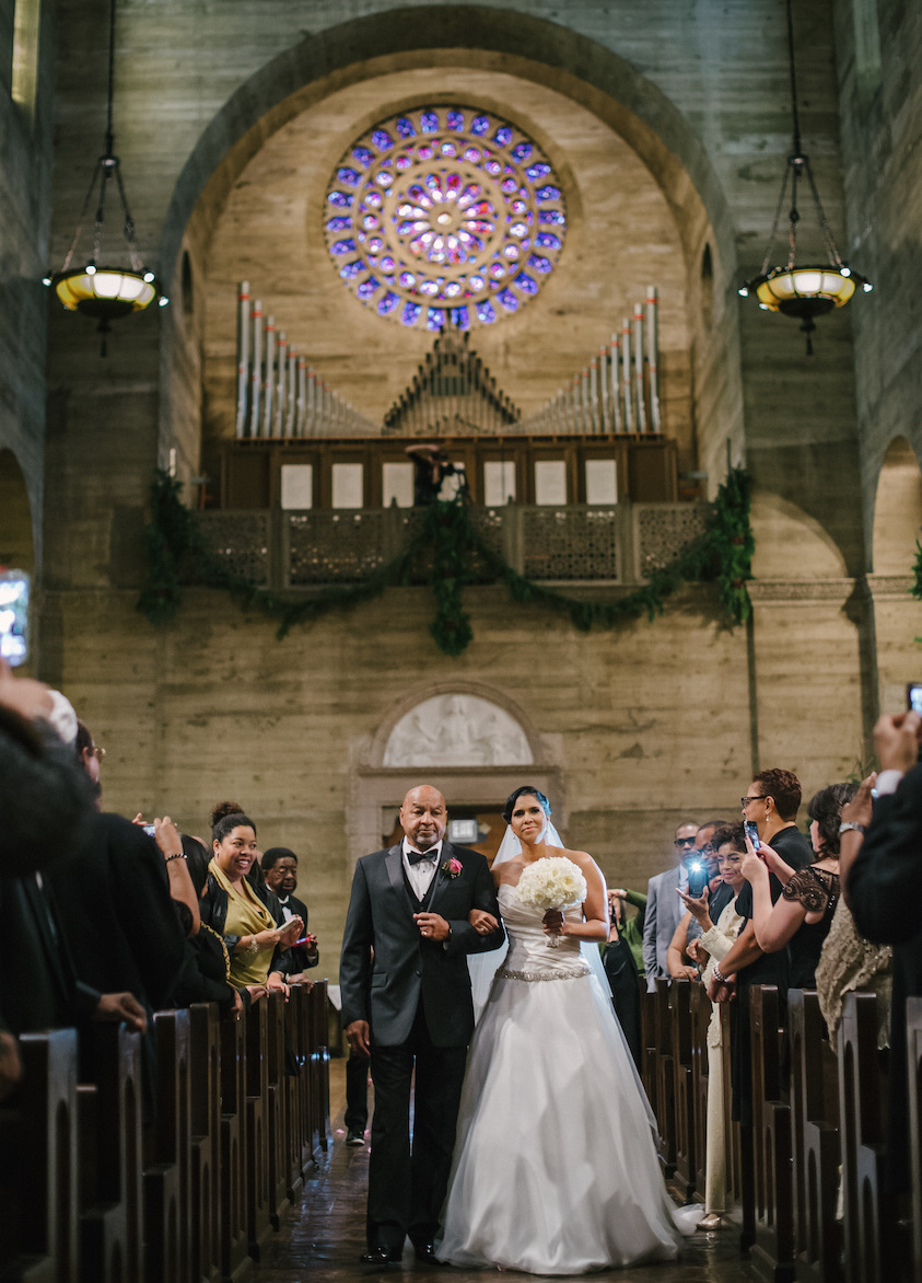 African American bride walks down aisle with father of bride