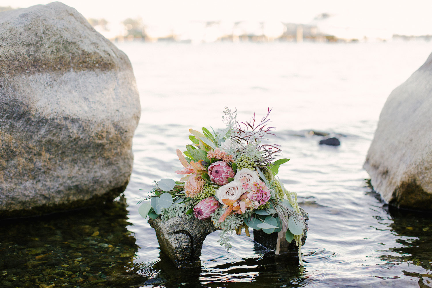 Protea organic wedding bouquet on rock in ocean