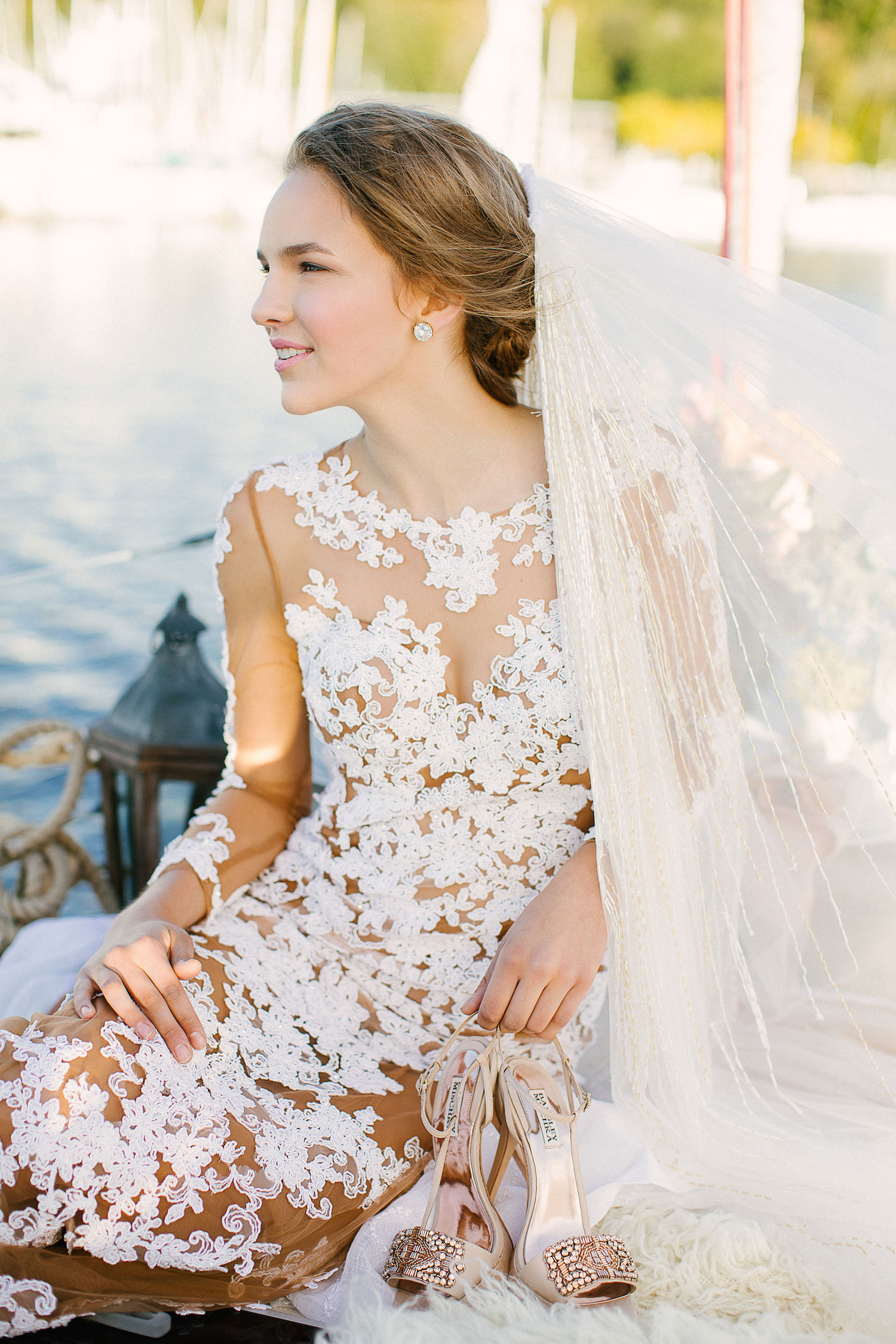 Bride on sailboat looking at sunset in sheer wedding dress