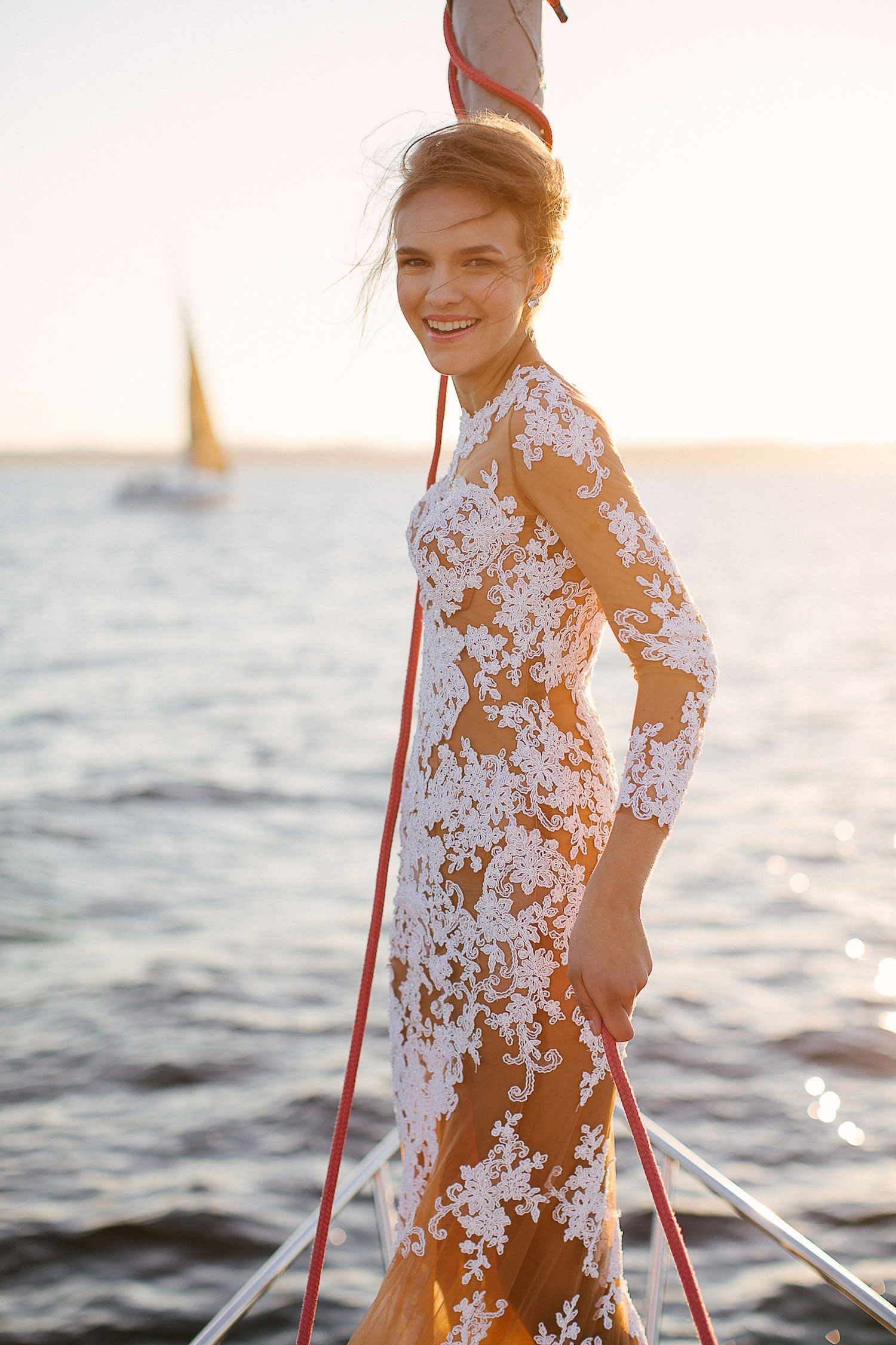 Bride in sheer long sleeve wedding dress on bow of sailboat