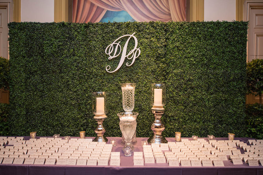 Hedge with monogram behind escort card table