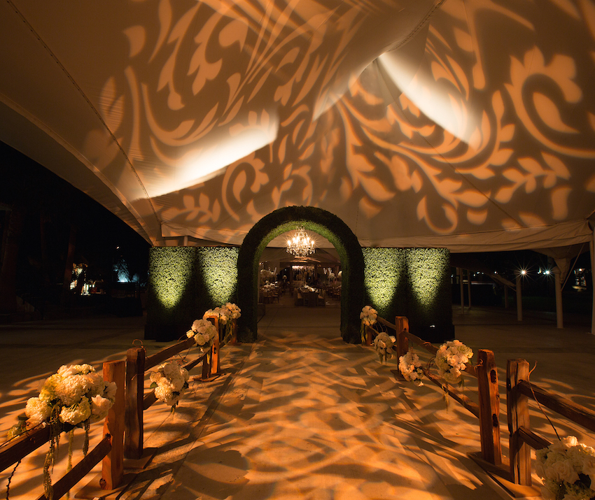 Arched hedge entryway into wedding tent
