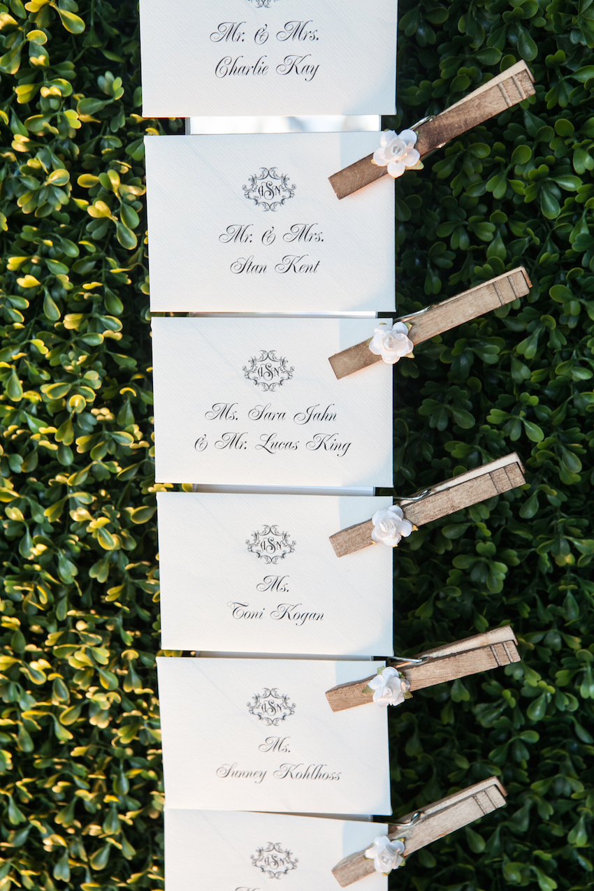 Place cards attached to hedge with clothespins