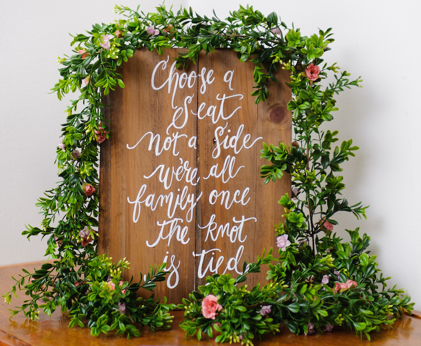 Wood sign with modern calligraphy at wedding