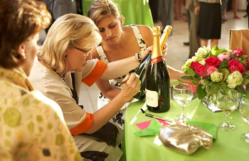 guests signing champagne bottle