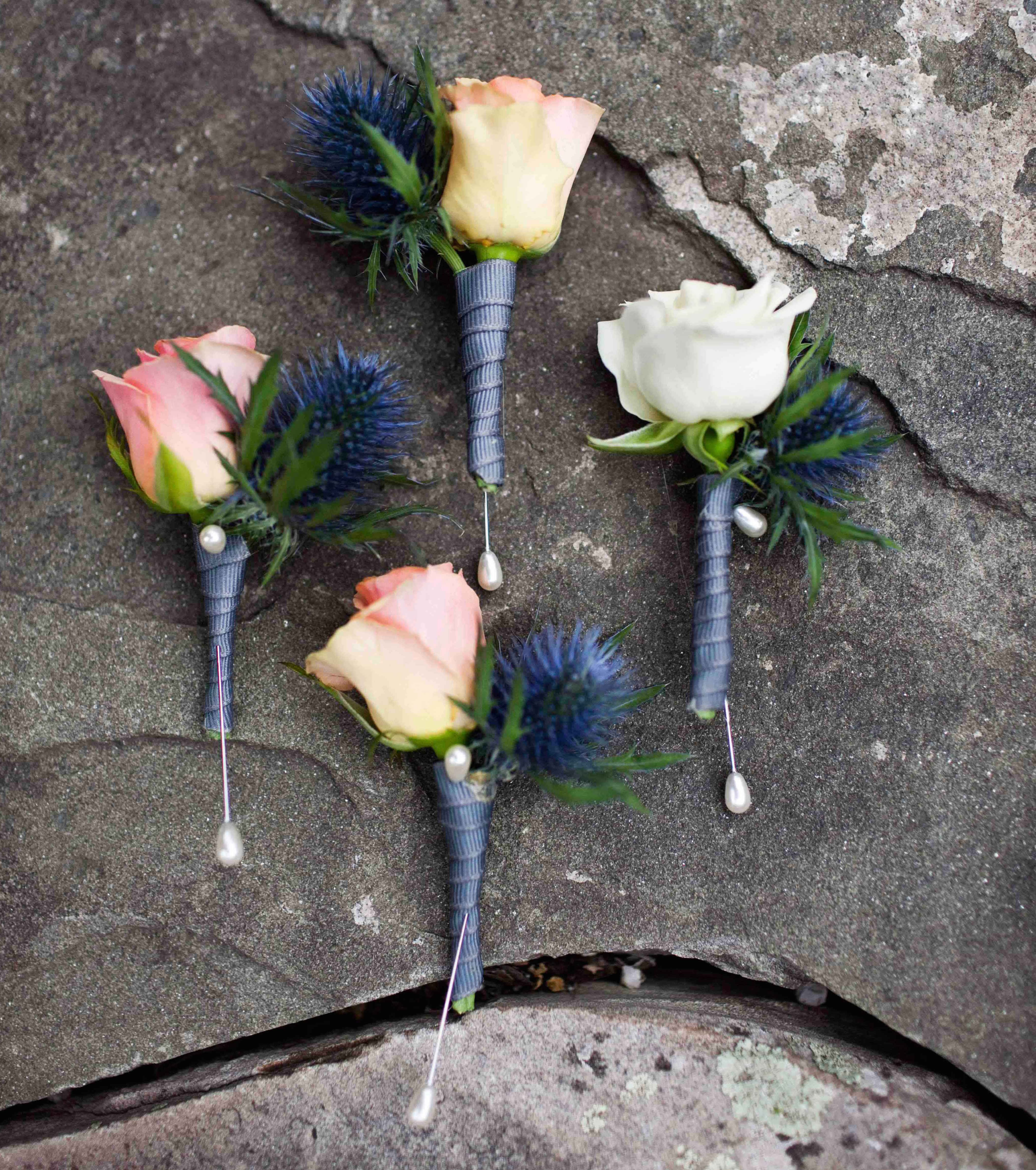 Rose boutonnieres with blue thistles