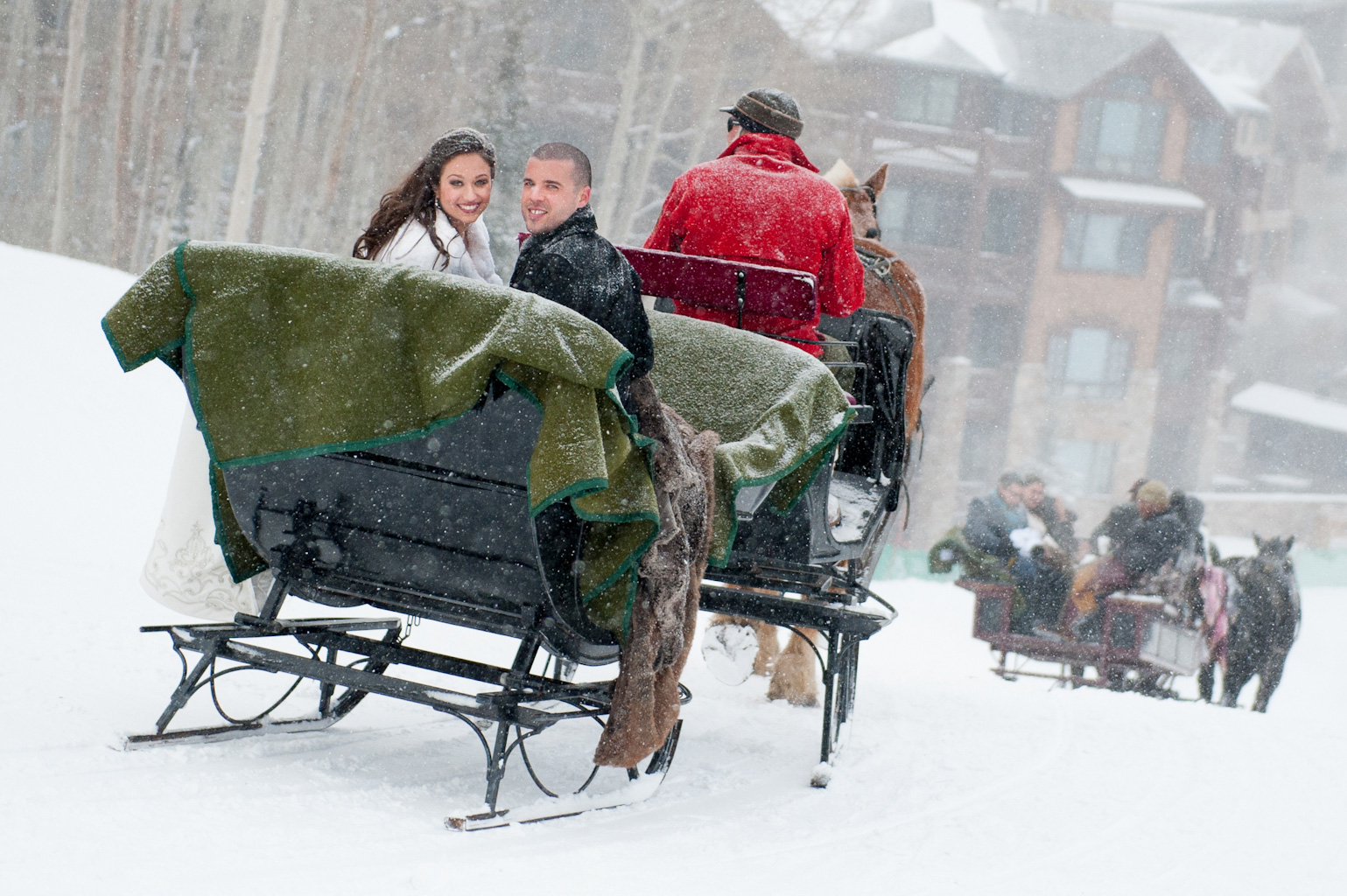 Bride and groom in horse drawn sleigh in snow