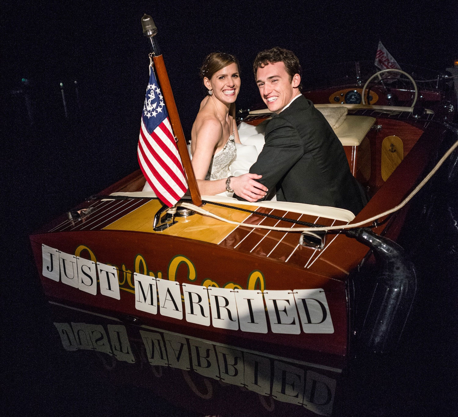 Bride and groom in Just Married wood boat