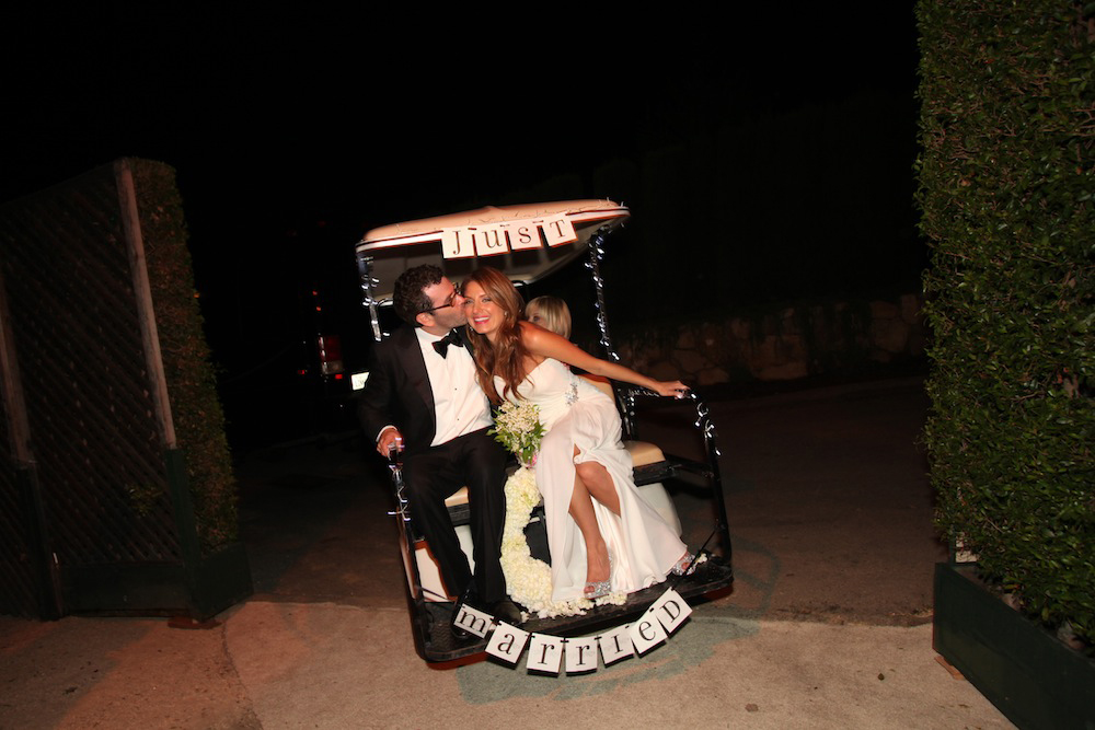 Bride and groom in Just Married golf cart