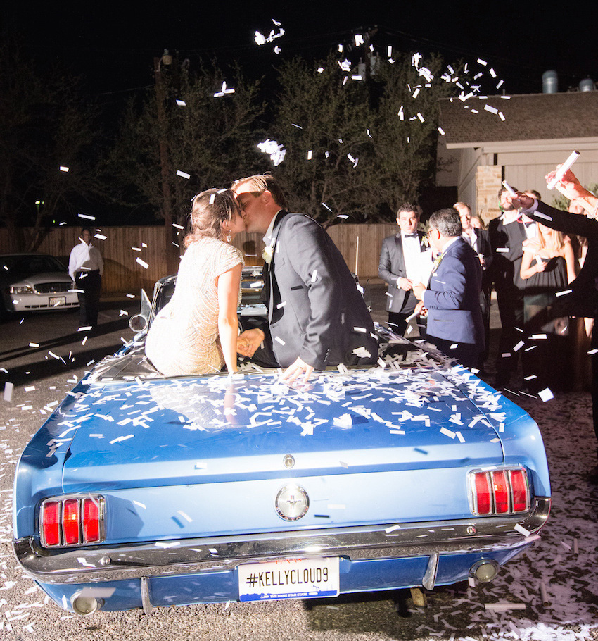 Bride and groom on top of blue Just Married Mustang