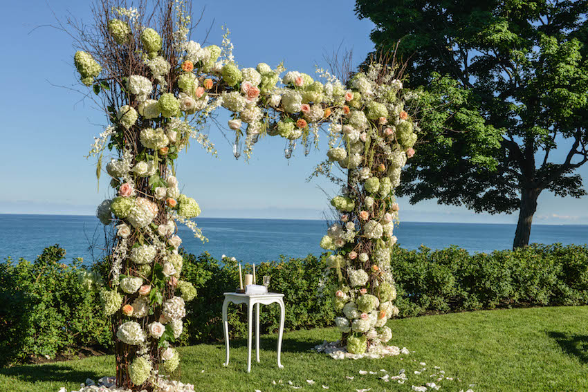 Outdoor wedding by lake with flower arch