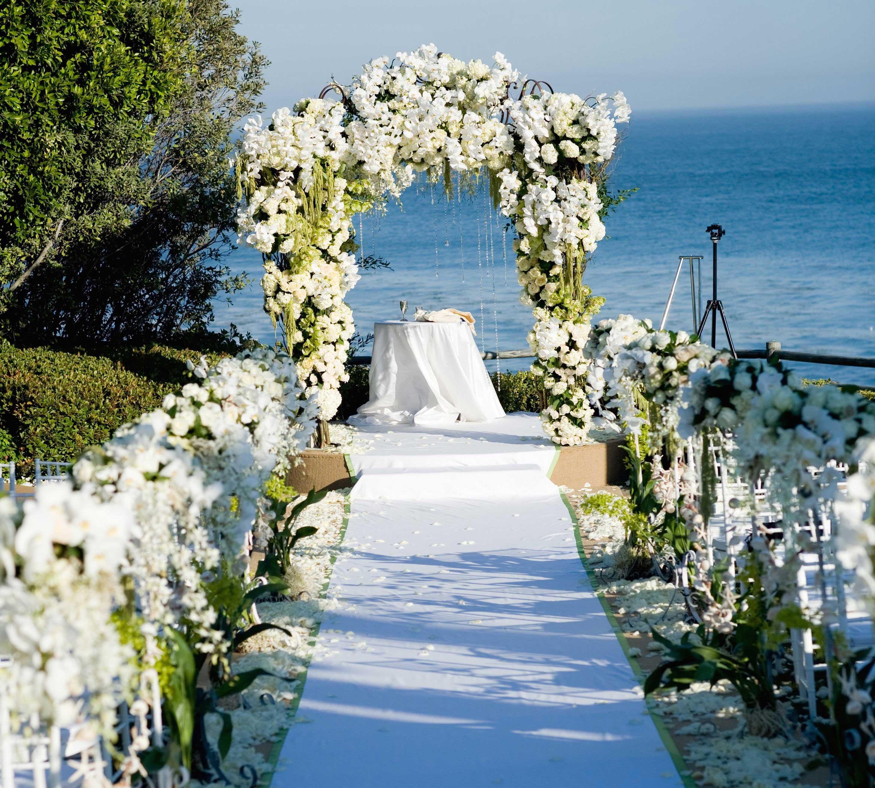Beach wedding ceremony with flower arch