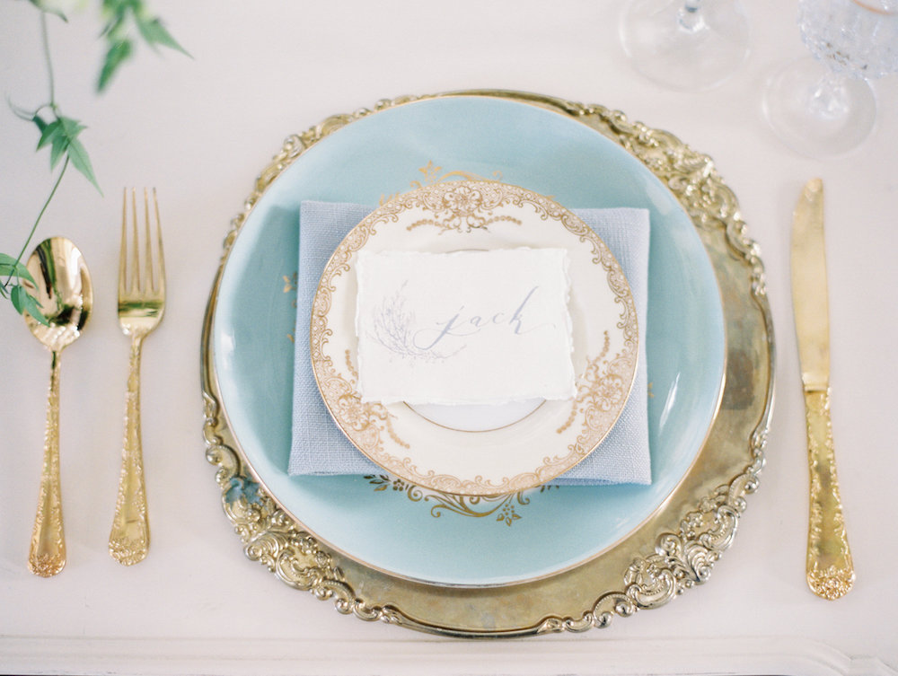 Gold flatware and light blue china wedding place setting