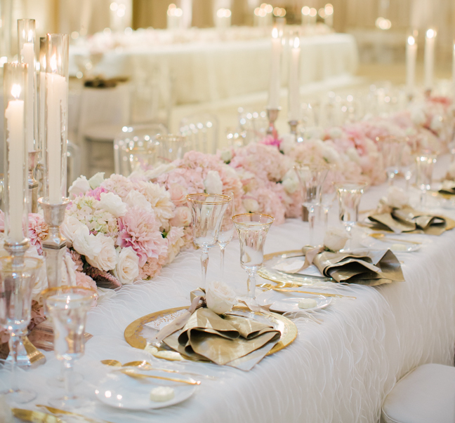 White and pink reception table with gold flatware