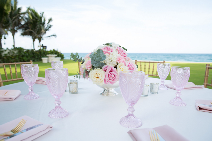 Pink crystal goblets and gold flatware at party
