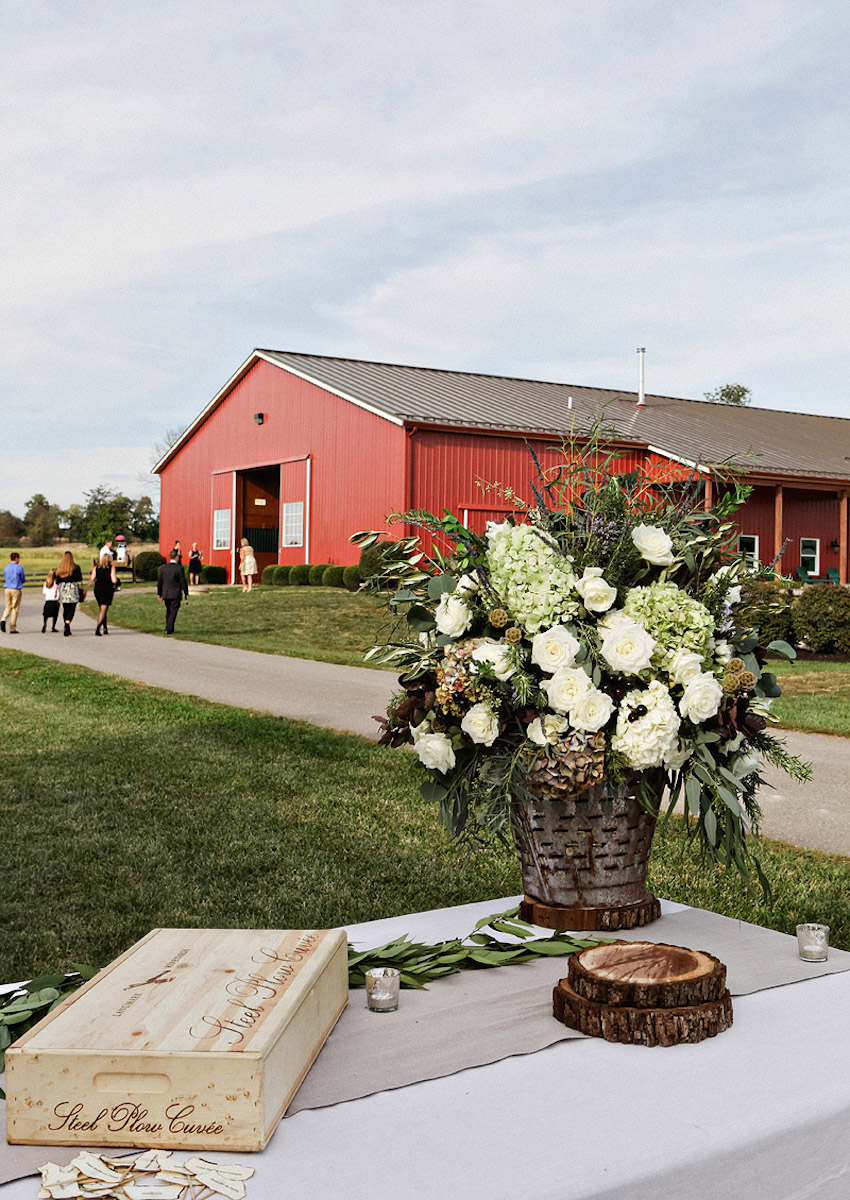Red barn in background with wedding guests