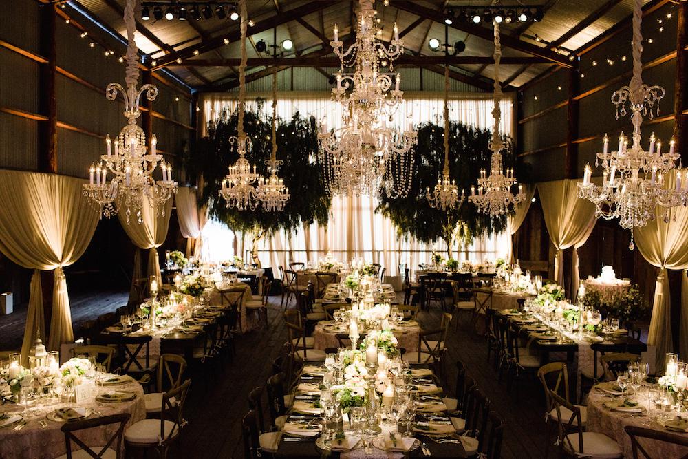 Candlelit barn wedding reception with chandeliers