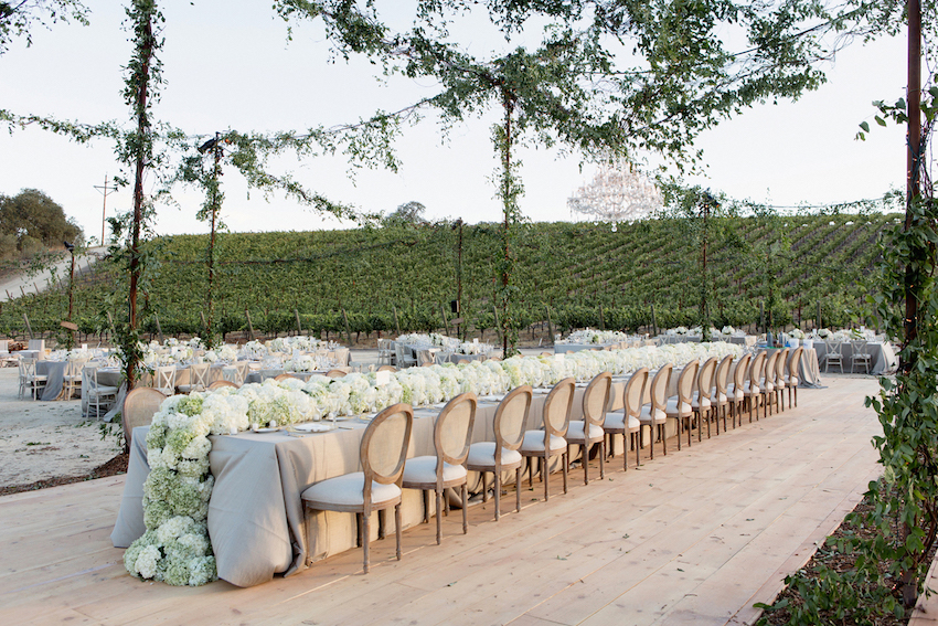 Green garlands on lighting at outdoor reception