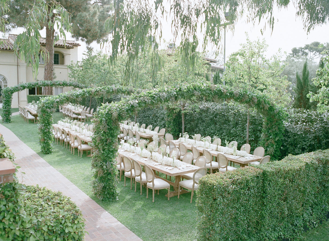 Green arches over tables at outdoor wedding