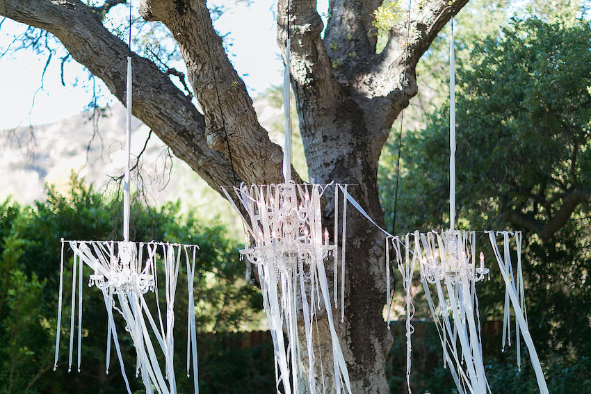 Ribbons hanging from chandeliers at outdoor wedding