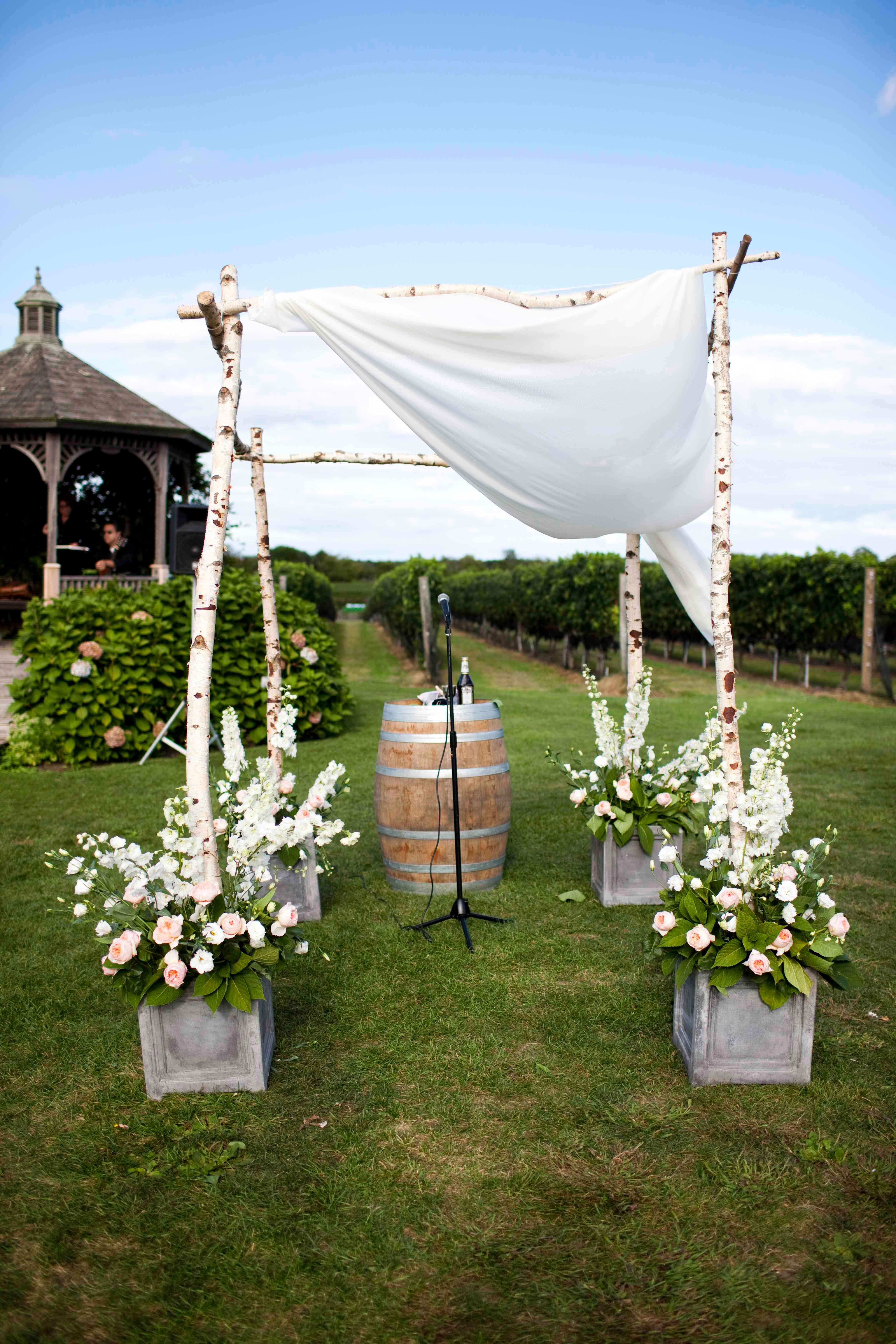 Birch tree trunk ceremony structure at outdoor wedding