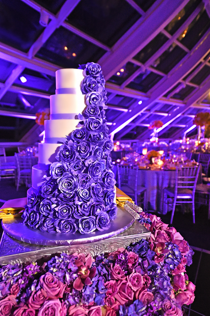 Cake table swathed in purple roses, orchids, and hydrangeas