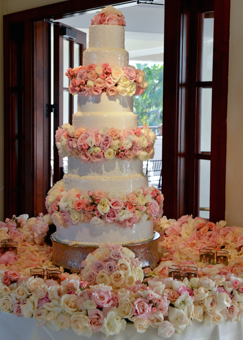 Tabletop ringed with blush and ivory roses for cake